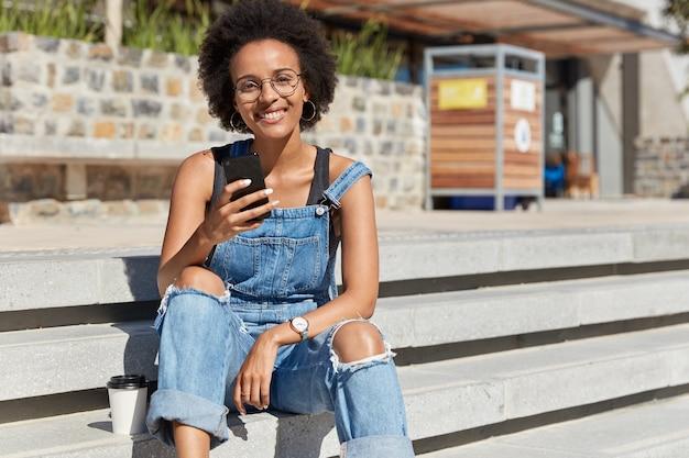 Vrouw met donkere huidskleur stuurt sms op mobiel, chat in sociale netwerken, draagt haveloze tuinbroek, zit aan de trap, geniet van wegwerpkoffie, recreatietijd op straat. zorgeloze tiener met apparaat