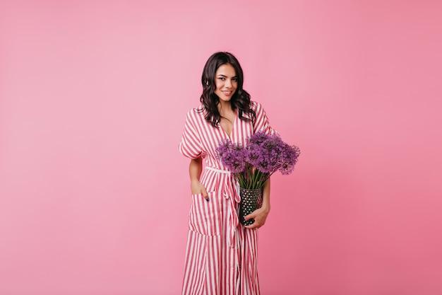Vrouw met donkere huidskleur vol vertrouwen in roze kamer. dame in lange zomerjurk houdt vaas met bloemen vast.