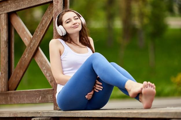 Vrouw met draadloze koptelefoon sloot haar ogen terwijl ze naar muziek luisterde in de natuur