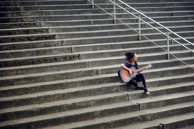Vrouw met dreadlocks alleen zittend op de trap van een universiteit gitaar spelen. 2