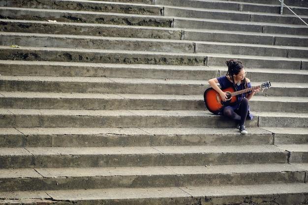 Vrouw met dreadlocks alleen zittend op de trap van een universiteit gitaar spelen. 3