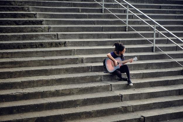Vrouw met dreadlocks alleen zittend op de trap van een universiteit gitaar spelen.