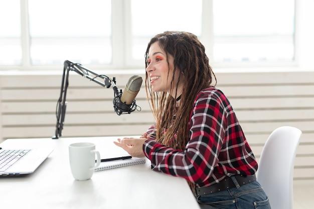 Vrouw met dreadlocks en glazen die bij de radio werken