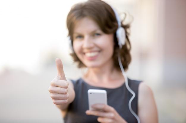 Vrouw met duim omhoog en hoofdtelefoons