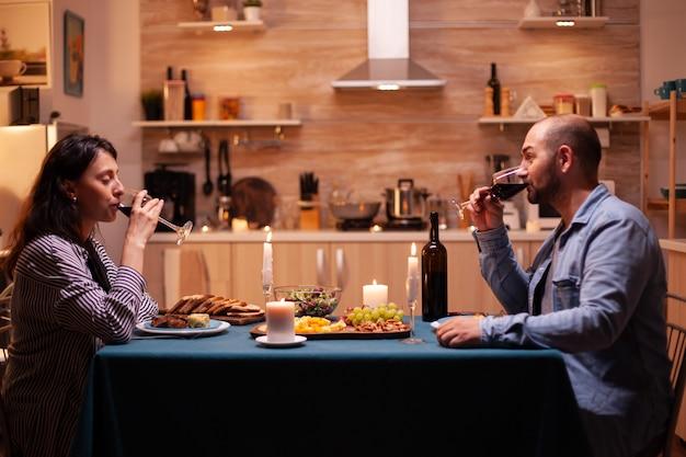 Vrouw met echtgenoot die rode wijn drinkt die van romantisch diner geniet. ontspan gelukkige mensen, zittend aan tafel in de keuken, genietend van de maaltijd, jubileum vieren in de eetkamer