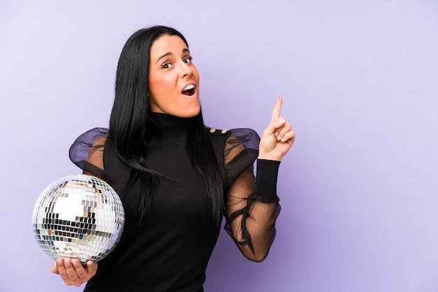 Vrouw met een bal partij geïsoleerd op paars naar de zijkant wijzend