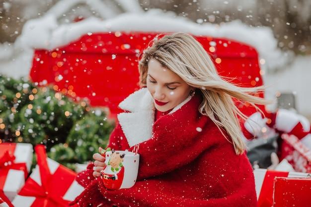 Vrouw met een beker met stier en zittend in de open auto met kerstdecor.