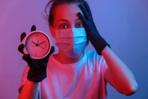 Vrouw met een beschermend masker, handschoenen houdt klok vast. rood blauw gradiënt neonlicht