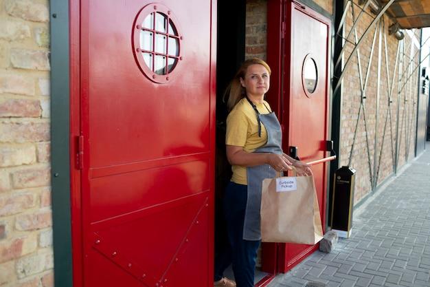 Vrouw met een bestelling voor een ophaling langs de stoep