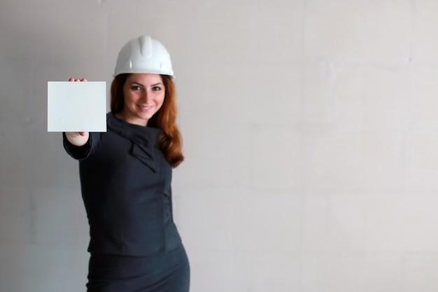 Vrouw met een blanco vel papier in zijn hand op een bouwplaats