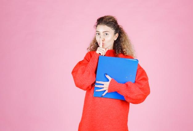 Vrouw met een blauwe map die om stilte vraagt.