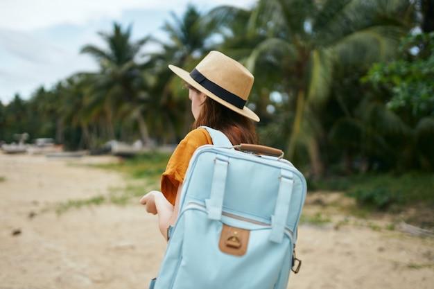 Vrouw met een blauwe rugzak in een gele jurk en hoed loopt langs de oceaan langs het zand met palmbomen