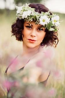Vrouw met een bloemenkrans op haar hoofd poserend in een veld