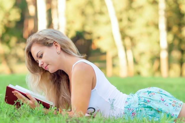 Vrouw met een boek. portret van een mooie vrouw met een boek. de vrouw over de aard. vrouw leest een boek.