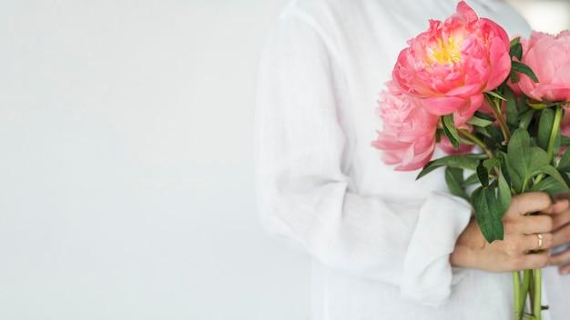 Vrouw met een boeket pioenrozen