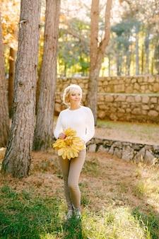 Vrouw met een boeket van gele herfstbladeren in lichte kleren
