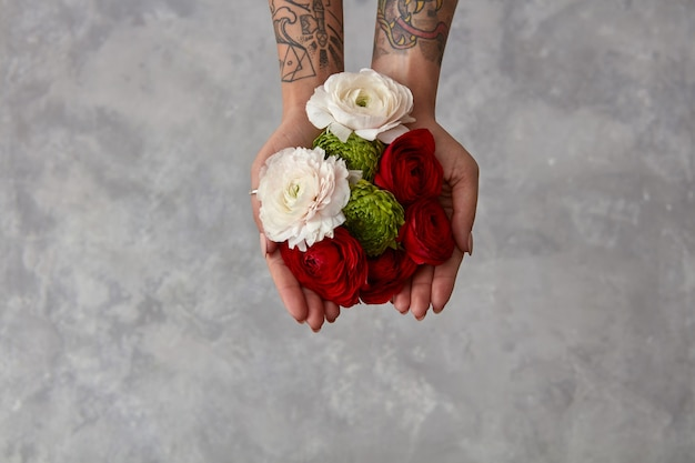 Vrouw met een boeket verse bloemen op een grijze achtergrond. het concept van een wenskaart. valentijnsdag bovenaanzicht