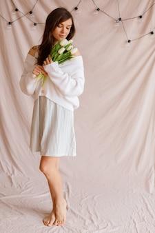 Vrouw met een boeket witte tulpen op vakantie