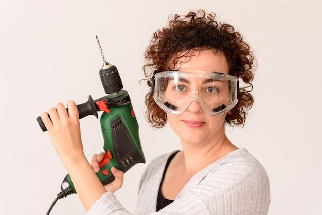 Vrouw met een boor klaar om huisverbeteringen aan te brengen
