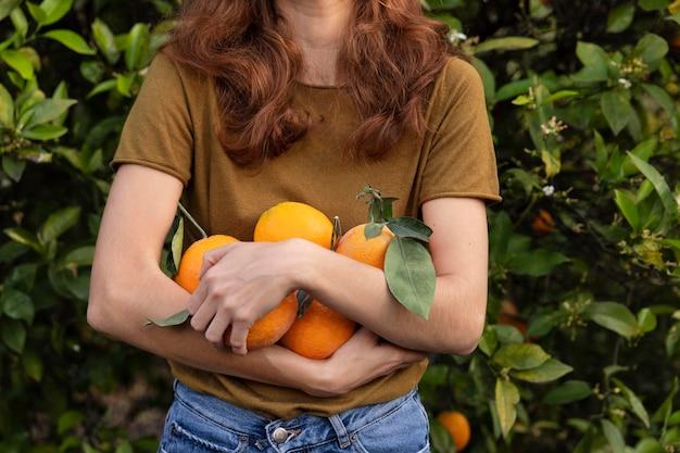 Vrouw met een bos sinaasappels orange