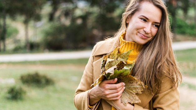 Vrouw met een bos van bladeren Gratis Foto