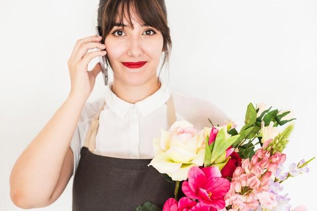 Vrouw met een bos van bloemen praten op mobiele telefoon