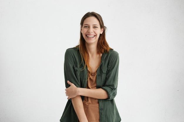 Vrouw met een brede glimlach gekleed in een groene jas en een bruin t-shirt glimlachend in het algemeen blij je te ontmoeten