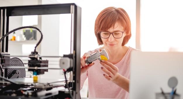 Vrouw met een bril die plastic details meet, gemaakt met een moderne 3d-printer
