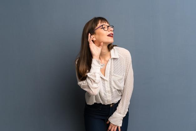 Vrouw met een bril over blauwe muur luisteren naar iets door hand op het oor te zetten