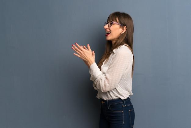 Vrouw met een bril over blauwe muur na presentatie in een conferentie applaudisseren