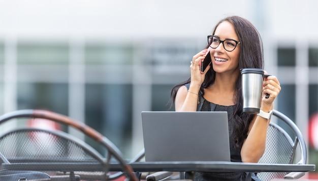 Vrouw met een bril praat aan een telefoon die lacht, een draagbare koffiemok vasthoudt en buiten het kantoorgebouw werkt.