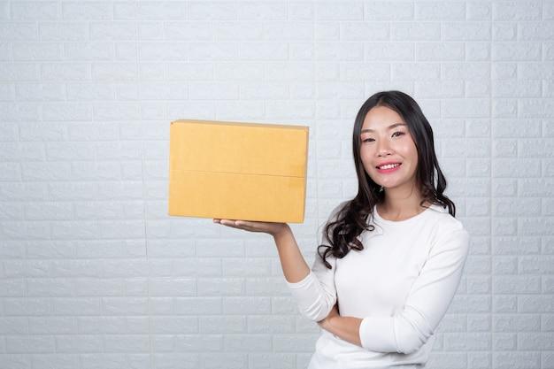 Vrouw met een bruine brievenbus gemaakt gebaren met gebarentaal.