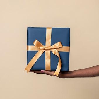 Vrouw met een cadeautje tegen een beige achtergrond