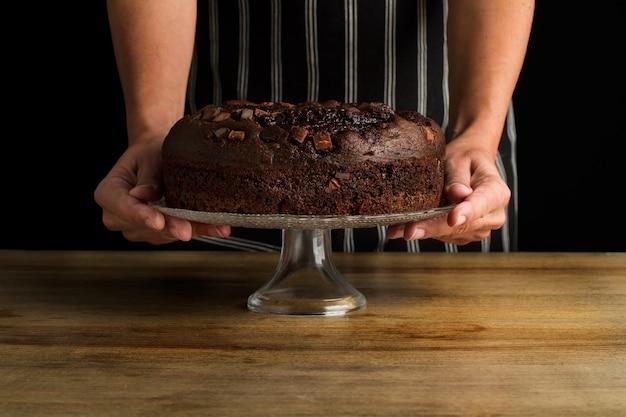 Vrouw met een caketribune met een chocoladetaart op een houten tafel