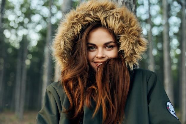 Vrouw met een capuchon op haar hoofd in een jasje koelte van de bosreis.