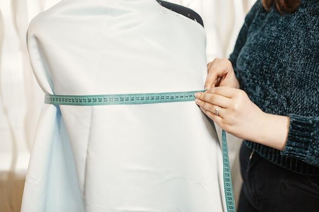 Vrouw met een centimeter om te meten. dame met bril. vrouw naait kleding