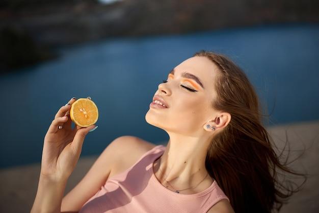 Vrouw met een citroen in haar handen, schoonheidshuidvoeding met vitamine c. natuurlijke cosmetica voor gezichtsverzorging. zonnige dag blauwe lucht