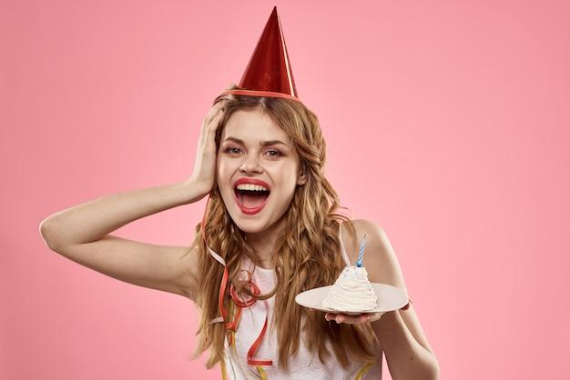Vrouw met een cupcake en een kaars in een feestmuts