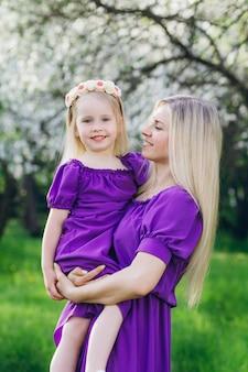 Vrouw met een dochtertje wandelen door de bloeiende appel