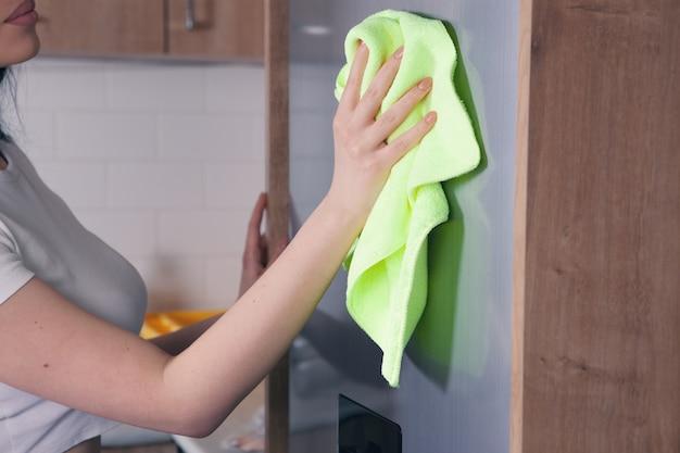 Vrouw met een doek om de koelkast schoon te maken