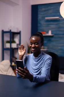Vrouw met een donkere huid zegt hallo tijdens een videoconferentie die 's avonds laat op kantoor aan het bureau zit. zwarte freelancer die werkt met een team op afstand dat virtuele online conferentie chat.