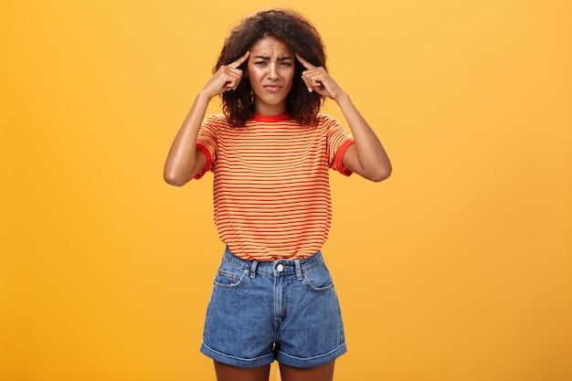 Vrouw met een donkere huidskleur die bezorgd kijkt en fronsend haar vingers op de slapen legt over de oranje muur