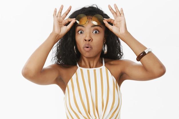 Vrouw met een donkere huidskleur die haar lippen vouwt en fluit van opwinding en verrassing, die er geïntrigeerd en verbaasd uitziet