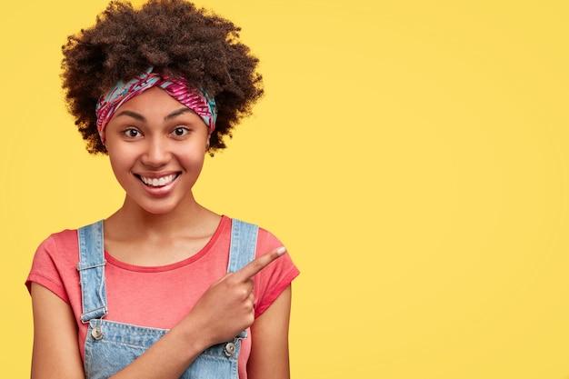 Vrouw met een donkere huidskleur en een vrolijke uitdrukking, nonchalant gekleed, wijst naar de rechterbovenhoek, geïsoleerd over een gele muur, stelt voor om dit café te bezoeken. positieve afro-amerikaanse vrouw binnen