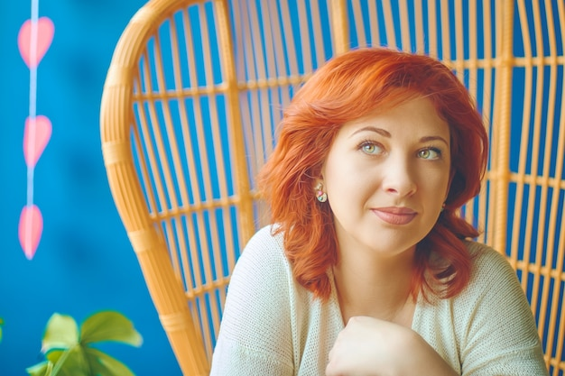 Vrouw met een doordachte dromen kijken zit in een café op een mooie stoel op valentijnsdag met een decor achter haar in de vorm van harten