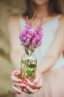 Vrouw met een doorzichtige glazen vaas met twijgen van roze bloemen en groene bladeren