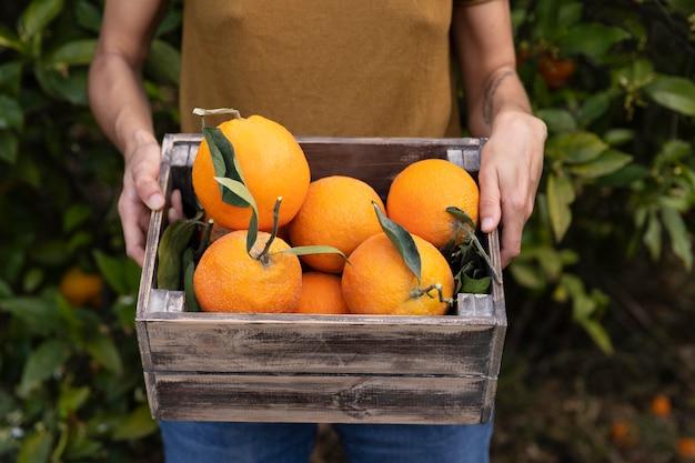 Vrouw met een doos vol sinaasappels in haar handen