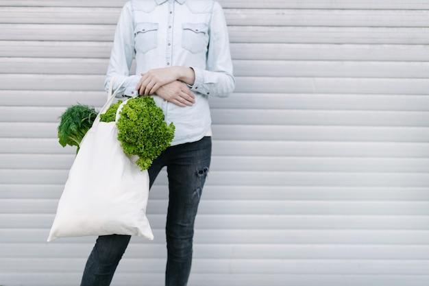 Vrouw met een eco-tas gevuld met kruidenier. groenten en fruit hangen aan een zak. ecologie of milieubescherming concept. witte eco-tas voor mock-up.