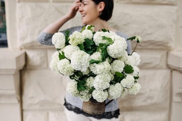Vrouw met een emmer met hortensiabloemen
