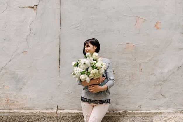 Vrouw met een emmer met seizoensgebonden witte bloemen